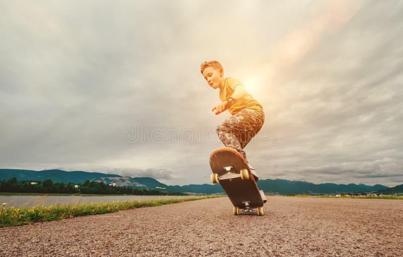 Junge macht einen Trick mit Skateboard stockfotografie