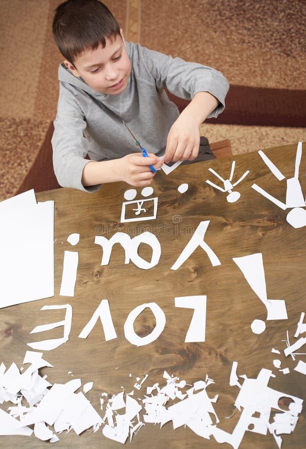 Junge macht Origami - Auto und Familie, Kinder, Elternteil, ich liebe dich Text, Draufsicht über hölzernen Hintergrund stockbilder