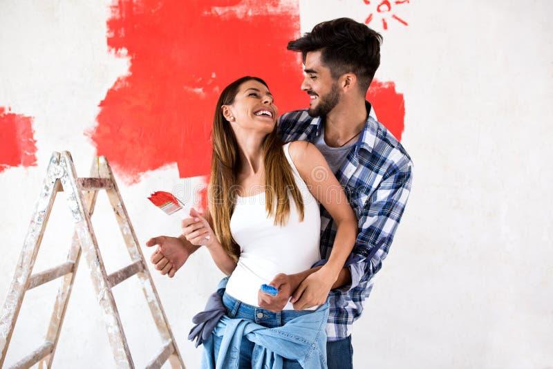 Junge Malereiwände des glücklichen Paars in ihrem neuen Haus lizenzfreie stockfotografie