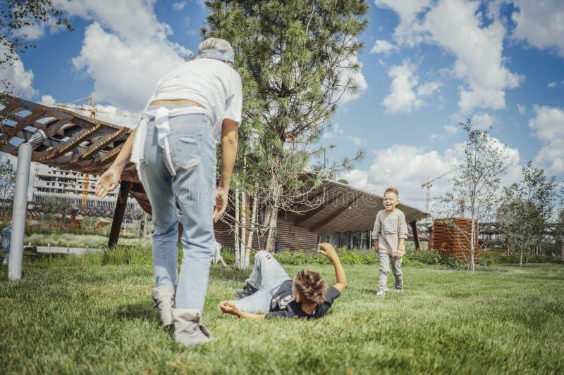 Junge Mama, die sich herum, wirbelnd mit ihren S?hnen am Park dreht Gl?ckliches Familienkonzept lizenzfreie stockfotografie