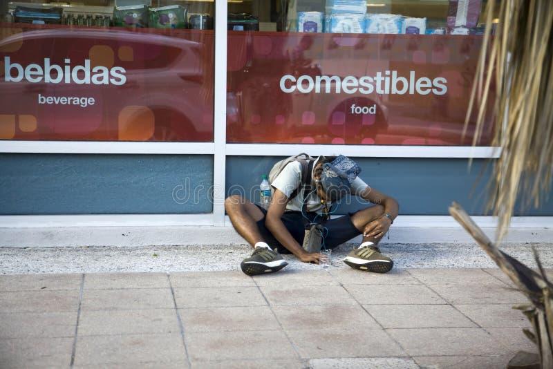 Junge Mann sitzt draußen und bettelt in Bayamon Puerto Rico lizenzfreie stockfotos