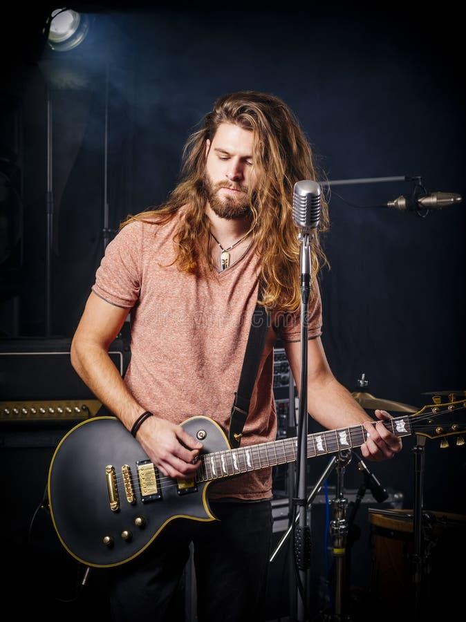 Junge Mann spielt E-Gitarre auf der Bühne lizenzfreie stockbilder