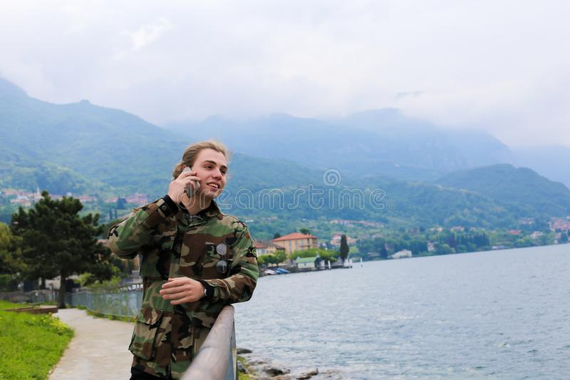 Junge Menschen mit langen Haaren, die mit Smartphone in der Nähe von Banister, See Como und Alpen Berg im Hintergrund sprechen lizenzfreie stockbilder