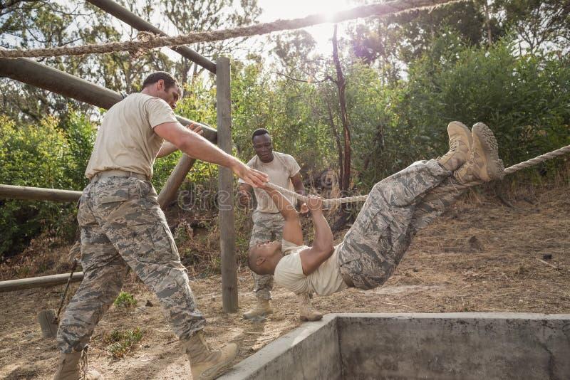 Junge Militärsoldaten, die das Seil klettert während des Hindernislaufs üben lizenzfreie stockfotos