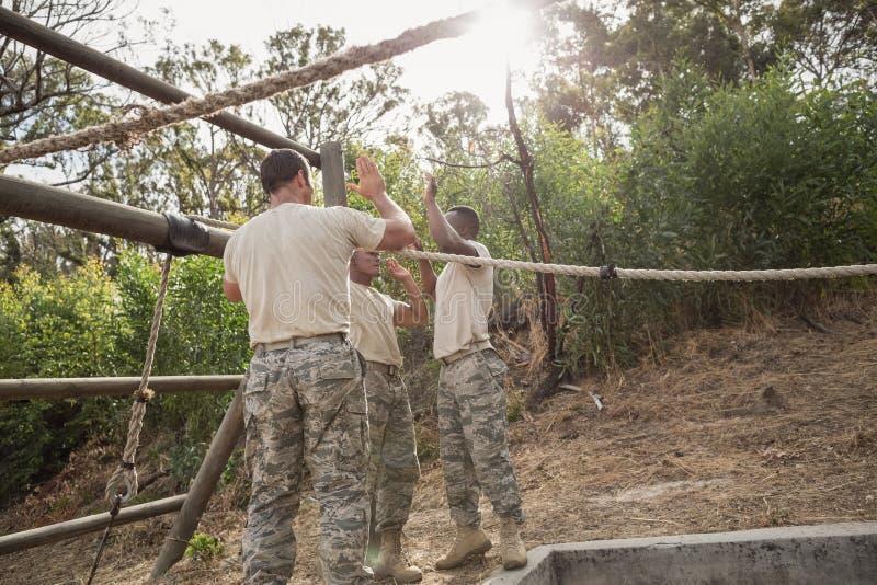 Junge Militärsoldaten, die nach dem Seil klettert während des Hindernislaufs geben stockbilder