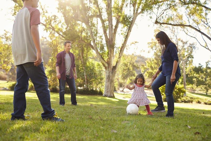 Junge Mischrassefamilie, die mit Ball in einem Park, Ernte spielt lizenzfreies stockbild