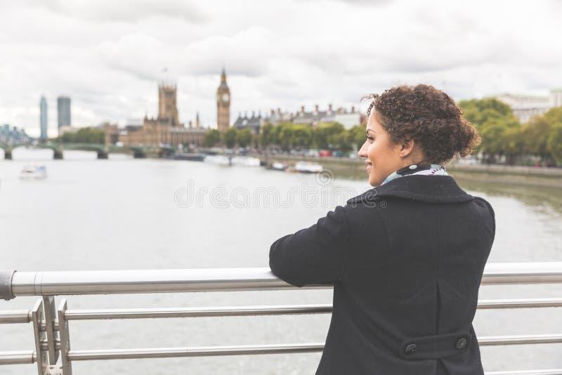 Junge Mischrassefrau auf einer Brücke in London stockfotografie