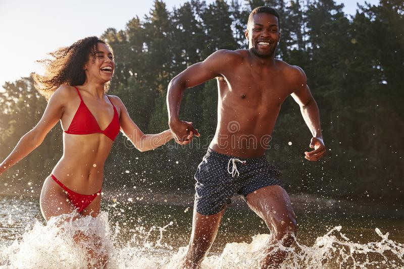 Junge Mischrassepaare, die in einen See laufen und spritzen lizenzfreie stockfotografie