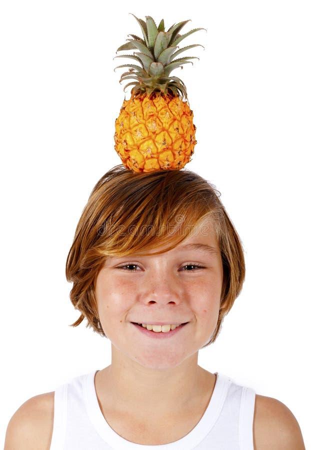 Junge mit Ananas auf seinem Kopf stockfoto