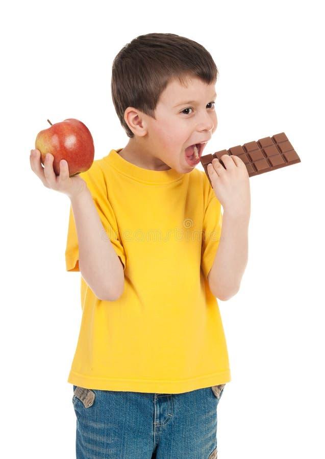 Junge mit Apfel und Schokolade lizenzfreies stockbild