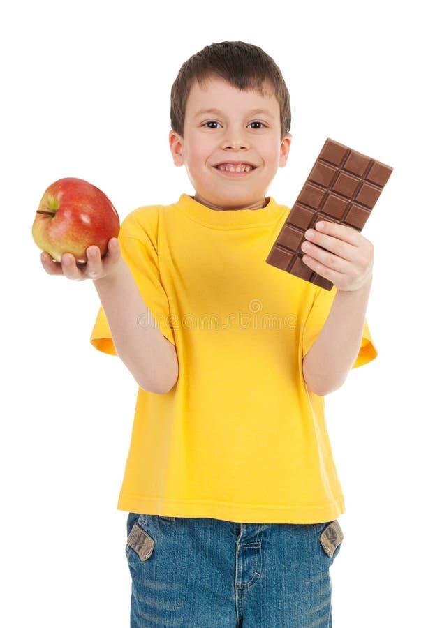 Junge mit Apfel und Schokolade stockfoto