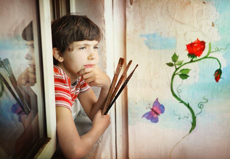 Junge mit Bürsten und seiner Malerei stockbild