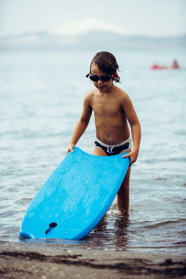 Junge mit bodyboard im Meer stockfotos