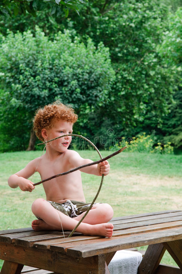 Junge mit Bogen und Pfeil stockfotografie