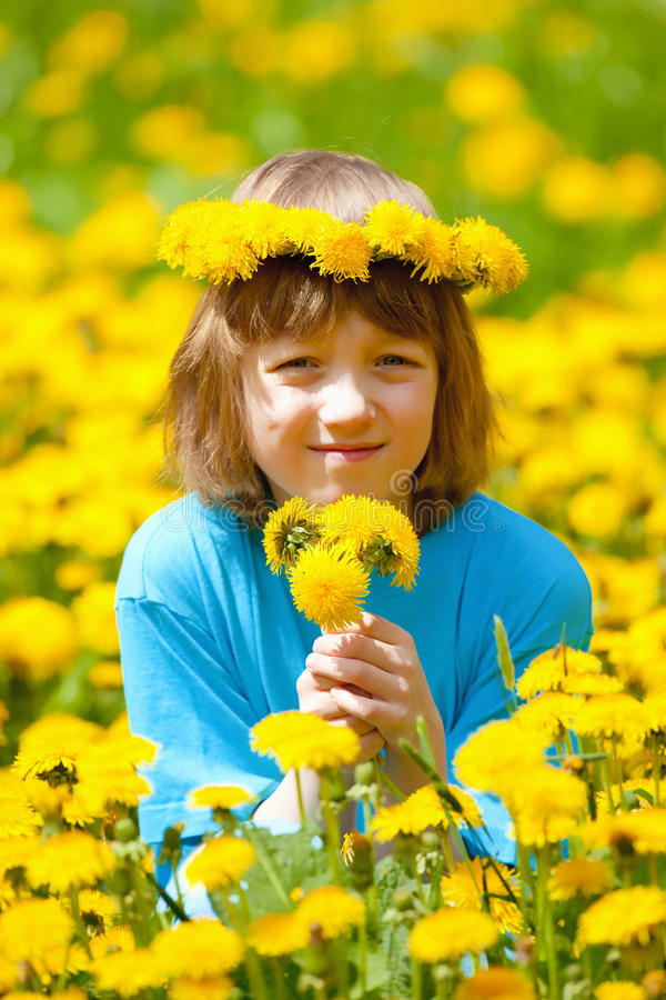 Junge mit dem Blumen-Kranz, der auf einem Löwenzahn-Gebiet sitzt lizenzfreies stockbild