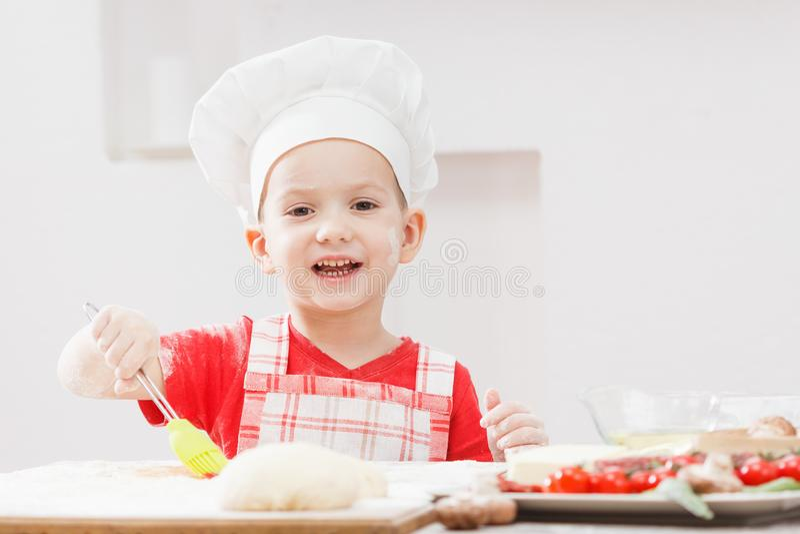 Junge mit dem Chefhut, der den Pizzateig zubereitet stockfotos