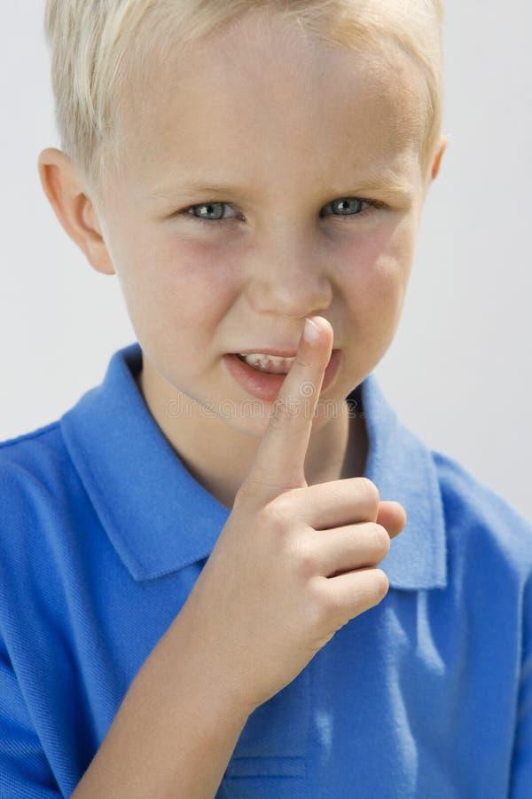 Junge mit dem Finger auf Lippen stockbilder