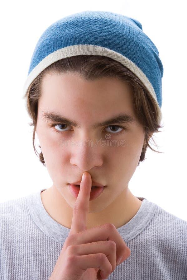 Junge mit dem Finger auf Mund stockfotografie
