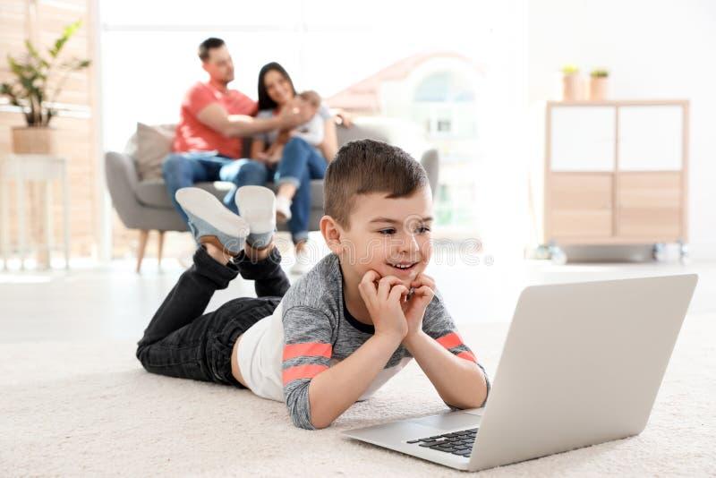 Junge mit dem Laptop, der auf Teppich nahe seiner Familie liegt stockbilder