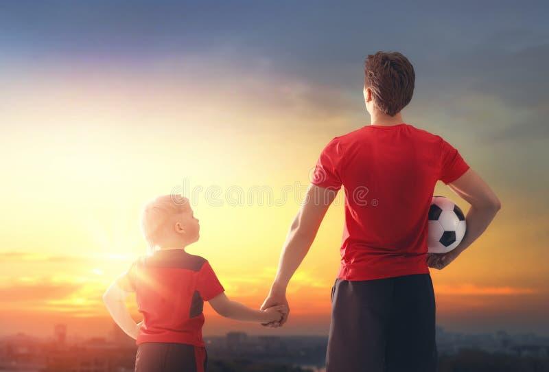 Junge mit dem Mann, der Fußball spielt stockfoto