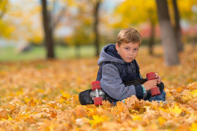 Junge mit dem Skateboard allein im Herbstpark lizenzfreie stockbilder