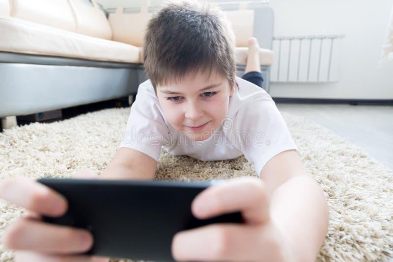 Junge mit dem Telefon, das auf einem Teppich im Raum liegt stockfotografie