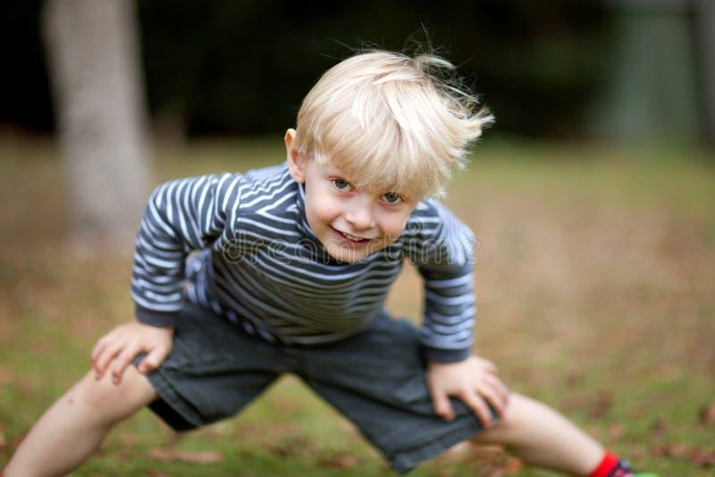 Junge mit den Händen auf Knie lizenzfreie stockbilder