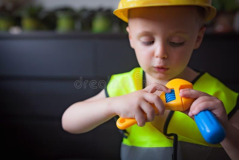 Junge mit einem Cheferbauersturzhelm stockfotos