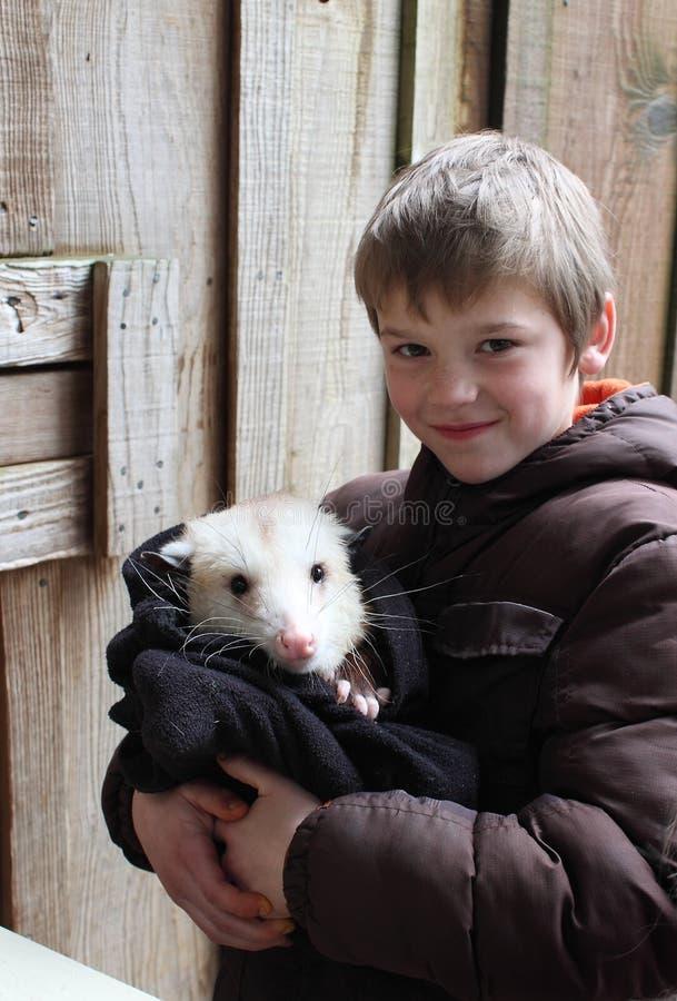 Junge mit einem Opossum stockfotografie