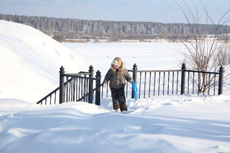 Junge mit einem Schlitten geht oben in den Winter lizenzfreies stockfoto