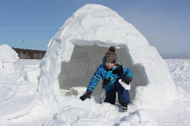 Junge mit einem Stück Schnee in seinen Händen kommt ein Iglu heraus lizenzfreies stockfoto