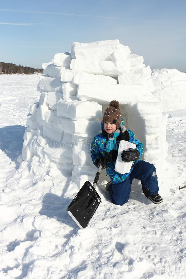 Junge mit einem Stück Schnee und eine Schaufel in seinen Händen, einen Iglu errichtend lizenzfreie stockfotografie
