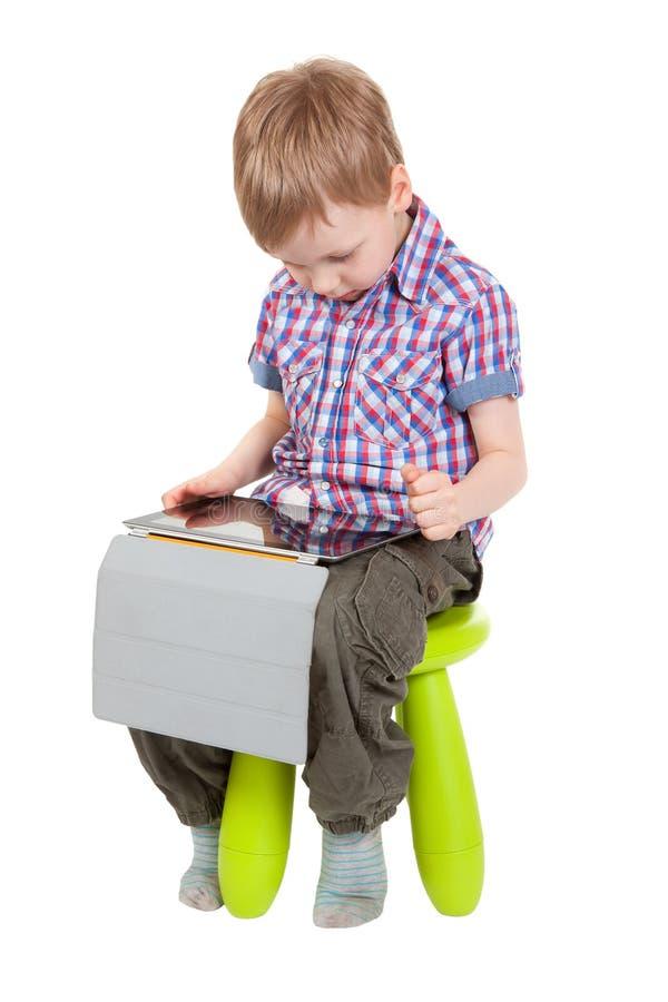 Junge mit einem Tablette PC, der auf einem Stuhl sitzt stockfotos