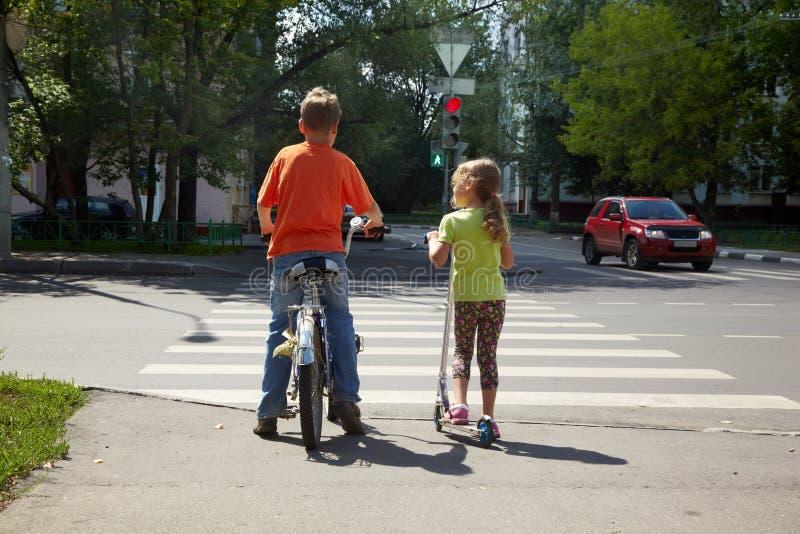 Junge mit Fahrrad und seine Schwester mit Roller stehen stockfotografie