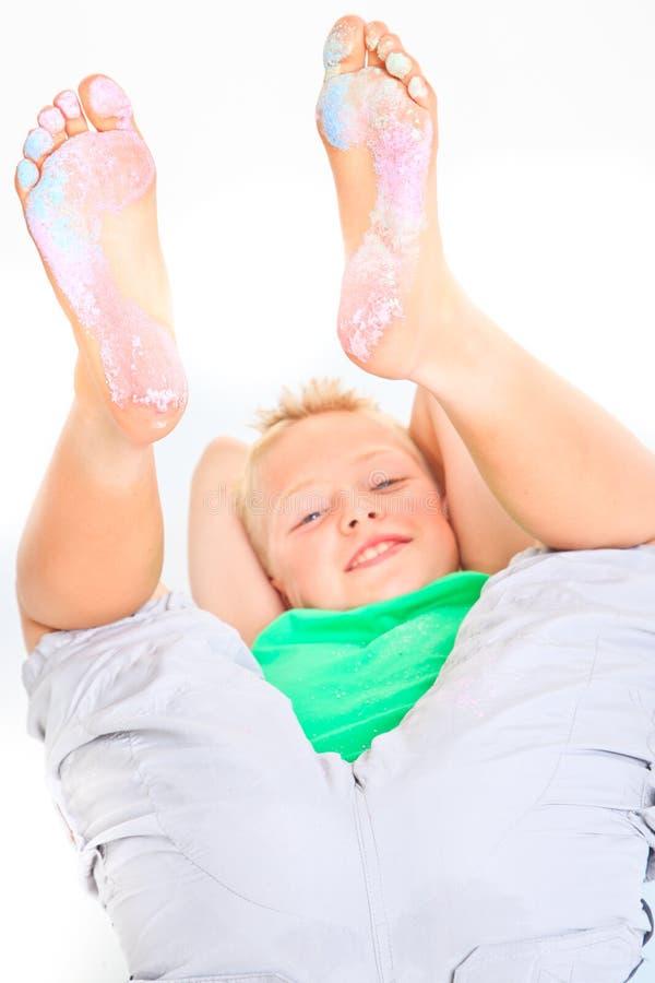 Junge mit farbiger Kreide auf seinen Füßen lizenzfreie stockbilder