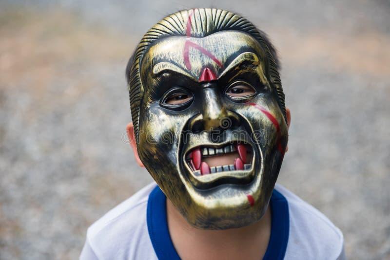 Junge mit furchtsamer Dracula-Metallmaske stockfoto
