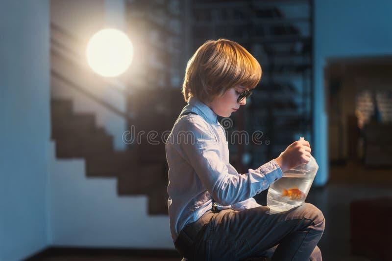 Junge mit Goldfisch in einem Öffentlichkeitswinkel des leistungshebels? e lizenzfreies stockbild