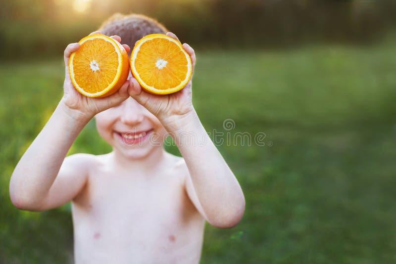 Junge mit Hälften von Orangen auf Augen Glückliches Kind, das Spaß hat lizenzfreie stockfotos