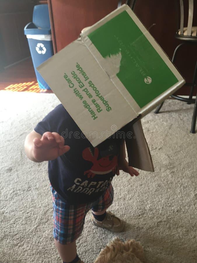 Junge mit Kasten auf Kopf stockbilder