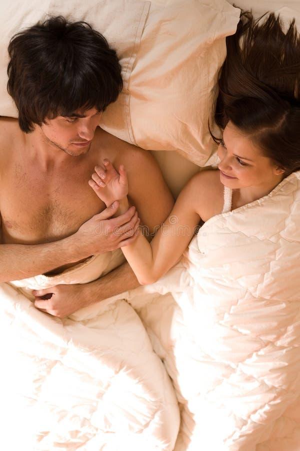Junge mit nettem Mädchen auf Bett lizenzfreies stockfoto
