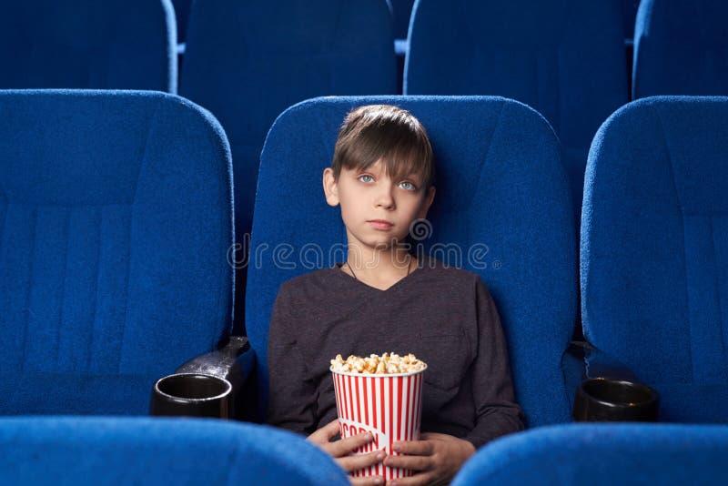 Junge mit Pokerface beim Betrachten von langweiligen Filmen im Kino stockbild