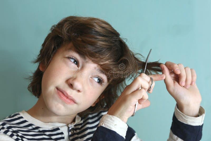 Junge mit Scheren versuchen, sein Haar zu schneiden stockfotos