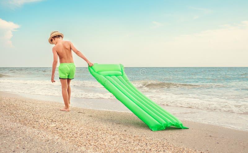 Junge mit Schwimmenmatratze geht auf Sandw?stestrand stockfotos