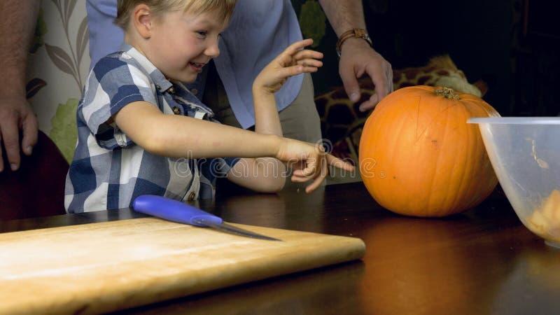Junge mit seinem Vater, der einen Kürbis für Halloween auf einer Tabelle schnitzt lizenzfreie stockbilder