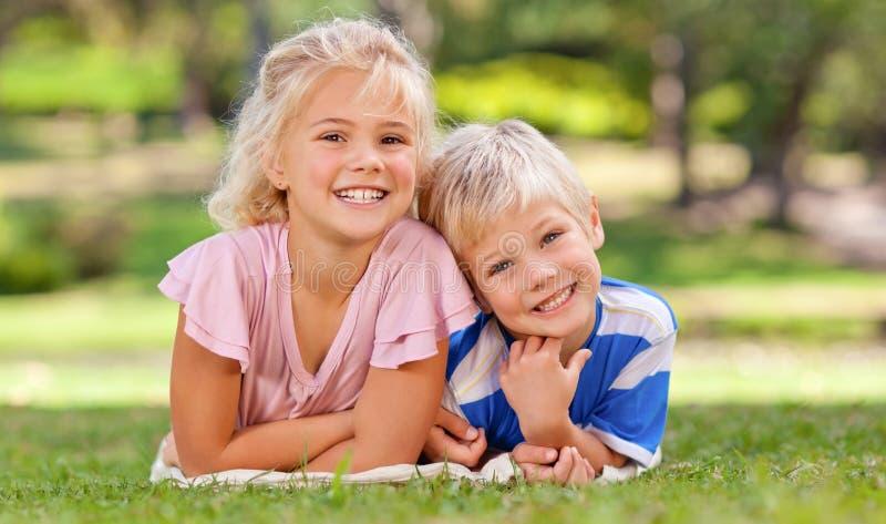 Junge mit seiner Schwester im Park stockfotografie