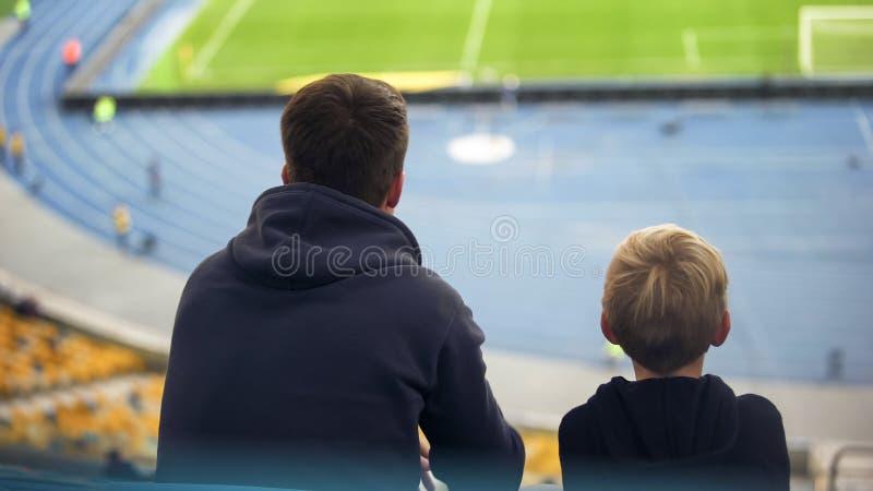 Junge mit sitzender Tribüne des Vaters am leeren Stadion, Fußballfane auf Exkursion stockfotografie