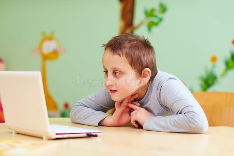 Junge mit Special muss Video durch den Laptop aufpassen stockfoto