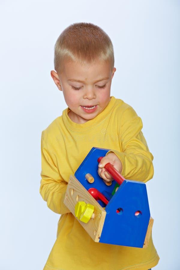 Junge mit Spielzeugwerkzeugkasten lizenzfreie stockfotografie
