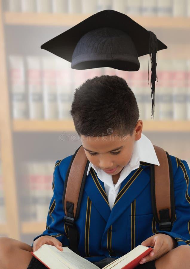 Junge mit Staffelungshut in der Bildungsbibliothek stockfoto