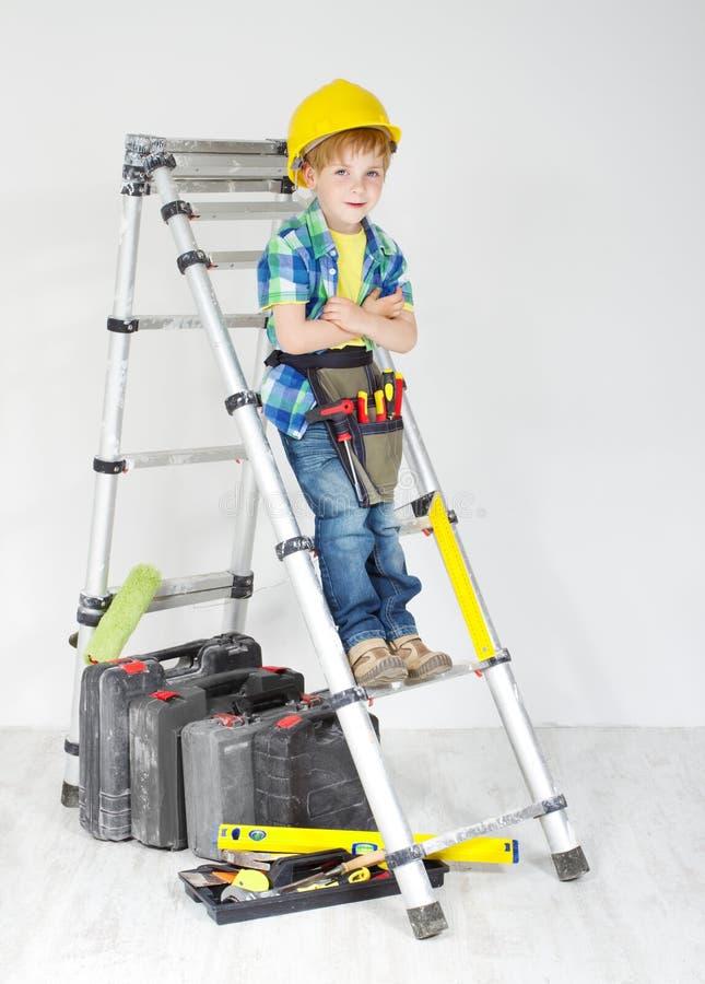 Junge mit Sturzhelm- und Hilfsmittelgurt auf Stepladder stockbilder